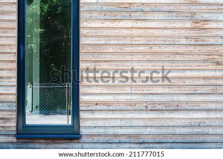 Modern window in a wooden plank wall - stock photo