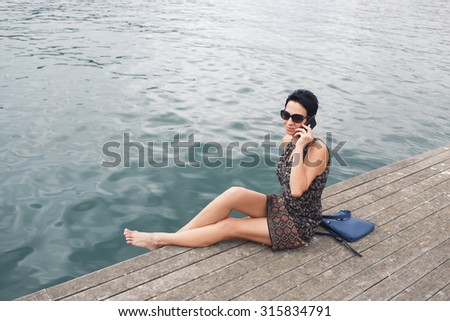 Modern woman having mobile phone conversation while sitting on a pier near sea background with copy space area for your advertising content, female talking on her cellphone while relaxing outside - stock photo