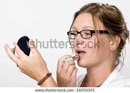 Modern woman putting on lipstick - stock photo