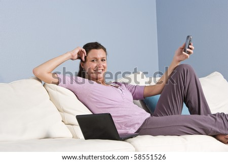 Modern woman relaxed on couch with mobile phone and laptop computer - stock photo