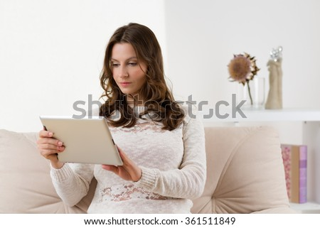 Modern woman with tablet in the living room. - stock photo