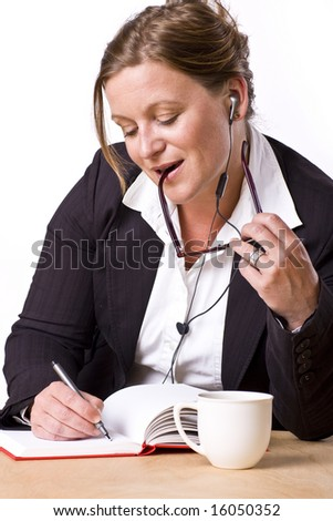 Modern woman writing in notebook with a satisfied expression and handsfree earplug. - stock photo