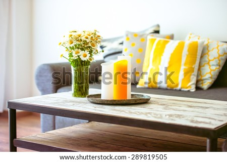 Modern wooden coffee table and cozy sofa with pillows. Living room interior and home decor concept - stock photo
