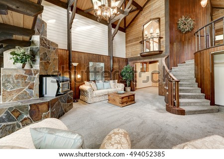 Modern wooden cottage interior with living room close up. Gorgeous fireplace with natural stone tile trim and circular staircase. Northwest, USA