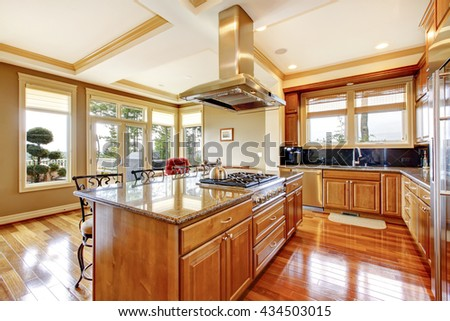 Modern wooden kitchen room design with hardwood floor, island, hood, granite counter top and view of the backyard. - stock photo
