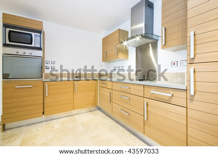 Modern wooden kitchen with silver appliances - stock photo