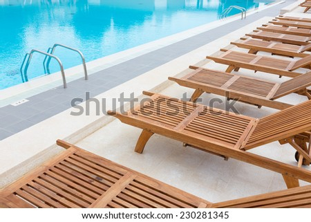 modern wooden sunbeds by turquoise swimming pool.  - stock photo