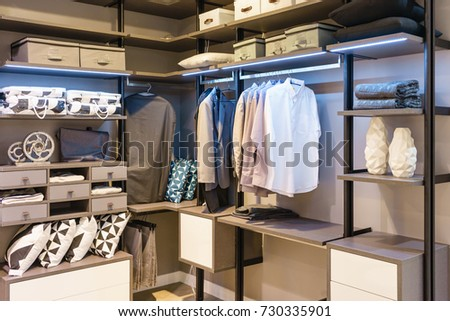 modern wooden wardrobe with clothes hanging on rail in walk in closet design interior