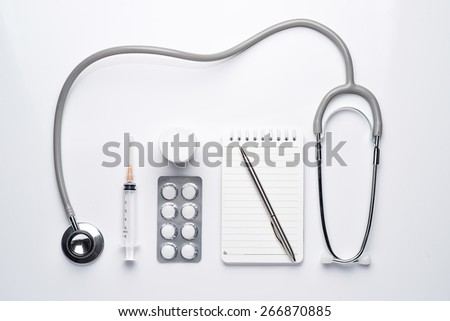 Modern workplace with a stethoscope, note, pen, pills and syringes. Medical concept. View from above - stock photo