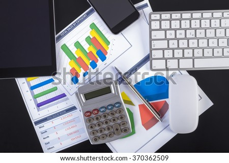 Modern workplace with digital tablet, pen, keyboard, mouse, smartphone and paper showing charts and diagram numbers on table.