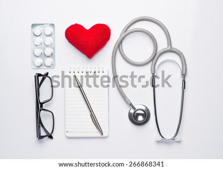 Modern workplace with heart, stethoscope, pills, note and eye glasses isolated on white background. Mecial care concept. View from the top - stock photo