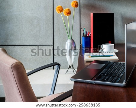 Modern workplace with laptop computer and flower vase on desktop - stock photo