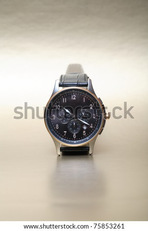 Modern wristwatch standing on nice silver background