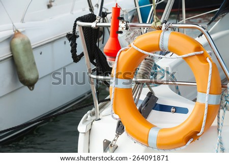 Modern yacht safety equipment, orange lifebuoy mounted on railings - stock photo