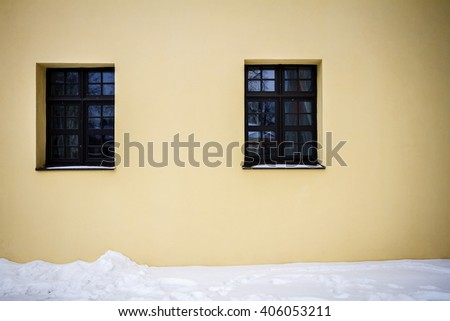 Modern yellow street wall with two windows