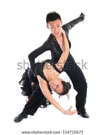 Modern young Asian teens couple latin dancers dancing in front of the studio background, full length isolated white. - stock photo