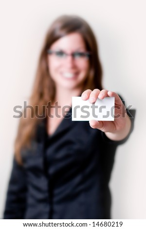 Modern young business woman holding out business card in air. Focus on business card and hand. Perfect for adding your own copy space.