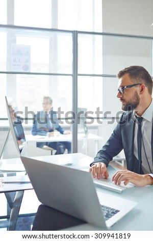 Modern young businessman sitting in front of computer and laptop and typing