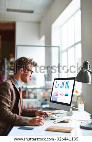 Modern young employee analyzing financial data in office - stock photo