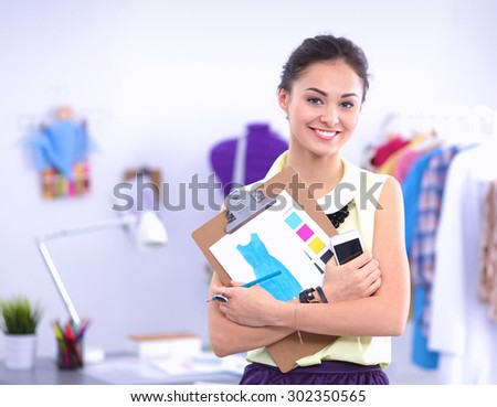 Modern young fashion designer working at studio - stock photo