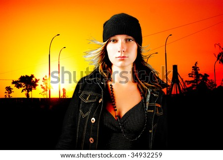 Modern young girl in jeans jacket in front of city sunset - stock photo