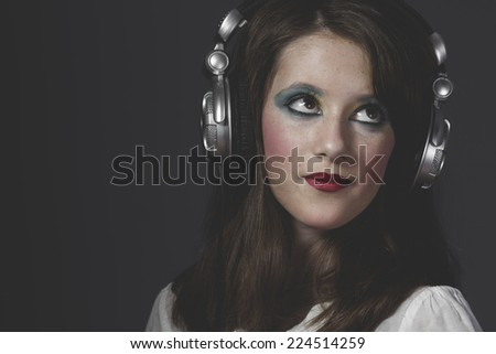 Modern, young girl listening music with huge headphones - stock photo