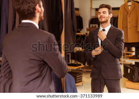 Modern young handsome businessman dressed in classical suit adjusting a tie in front of the mirror while standing in the suit shop - stock photo