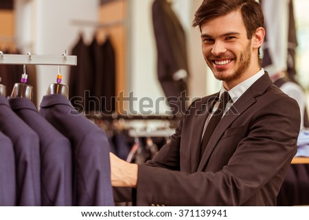 Modern young handsome businessman smiling, looking and choosing classical suit in the suit shop