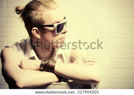 Modern young man in jeans clothes posing by the white brick wall. Youth fashion.  - stock photo