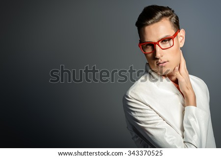 Modern young man in white jacket and elegant red glasses. Studio fashion shot. Optics.