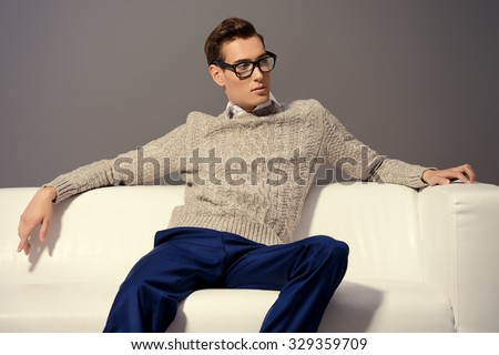 Modern young man sitting relaxed on a sofa. Men's beauty, fashion. - stock photo