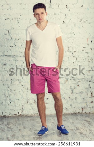 Modern young man. Young modern man stands against a white brick wall. A man wearing clothes - white shirt, pink shorts and blue sneakers. Man in full growth. Man looks serious look. Modern concept. - stock photo