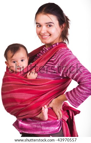 Modern young mother carrying her baby in a sling - stock photo