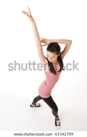 Modern young woman dancing and posing, full length portrait on white background.