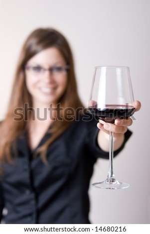 "Modern young woman holding a wine glass with liquid in it doing a ""cheers"" motion. Focus in glass."