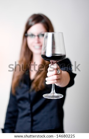 "Modern young woman holding a wine glass with liquid in it doing a ""cheers"" motion. Focus in glass. Glass is slightly covering woman's face."