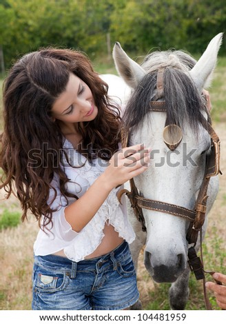 Modern young woman talking to her favorite horse