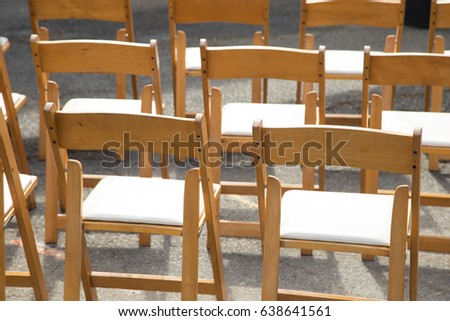 Modest Collapsible Wood Folding Chairs With White Cushion Seats Arranged In Rows At Outdoor Wedding Event
