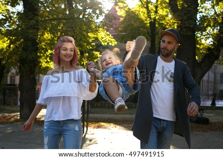 Modish parents hold their little daughter while whirling she in the air