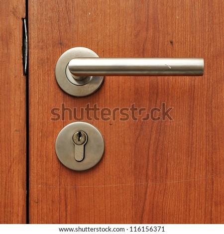 Modren style door handle on natural wooden door - stock photo
