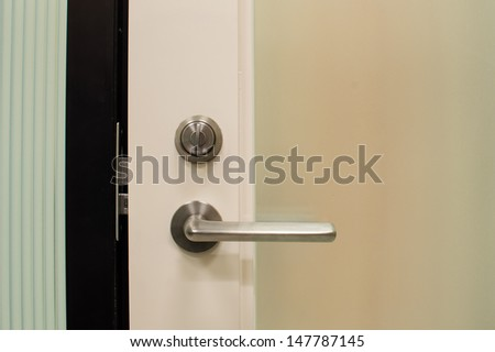 Modren style door handle on natural wooden door.