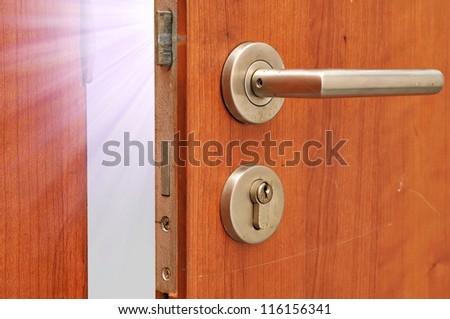 Modren style door handle on natural wooden door with white light - stock photo