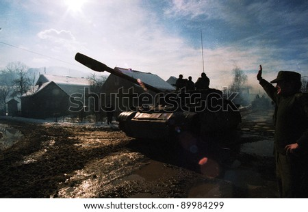 MODRICA, BOSNIA - JAN 8: A Bosnian Serb T-54 tank passes through Modrica, Bosnia, on Friday, January 8, 1995. The tank had just taken part in an extensive ethnic cleansing operation south of Modrica. - stock photo
