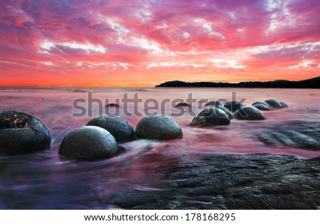 Moeraki Boulders on the Koekohe beach, Eastern coast of New Zealand. Sunset and long exposure - stock photo
