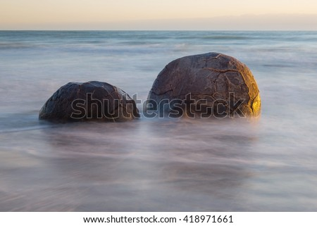 Moeraki Boulders on the Koekohe beach, New Zealand during sunrise (long exposure)