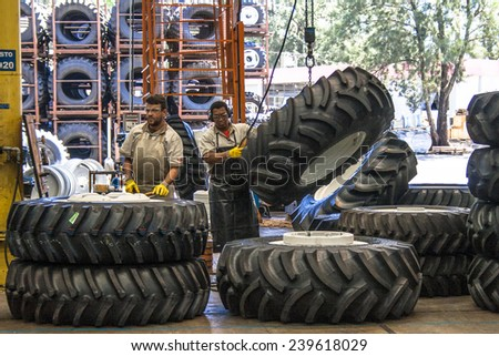 Mogi da Cruzes, Sao Paulo, Brazil, Septermber 19, 2008: Workers mount tractors at tractors and machines factory, in Brazil - stock photo