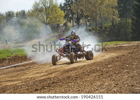 "MOHELNICE,  CZECH REPUBLIC - APRIL 19: Racer is riding a quad with a smoking engine in the ""International Championship of the Czech Republic 2014"" on April 19, 2014  in MOHELNICE, Czech Republic."