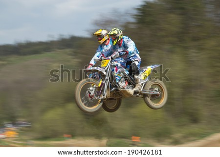 """MOHELNICE, CZECH REPUBLIC - APRIL 19. Two racers in blue are jumping a sidecar in the """"International Championship of Czech Republic 2014"""" on April 19. 2014  in the town of Mohelnice, Czech Republic.  - stock photo"""
