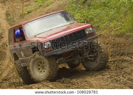 "MOHELNICE, CZECH REPUBLIC - JUNE 10. Unidentified racer at red off-road car on a steep slope in the ""SHOCK CUP Trial 2012"" on June 10, 2012 in the town of Mohelnice, Czech Republic."