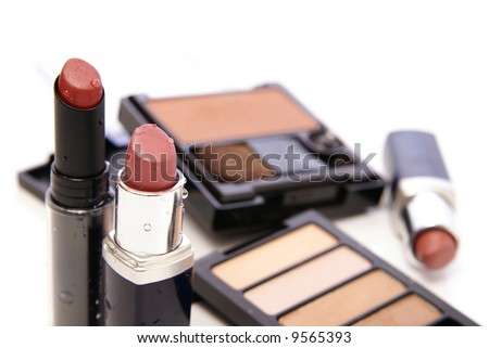 Moist lipsticks in earth tones with related makeup and cosmetics in the background